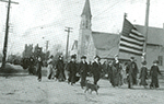 Big Annie Clemenc carries the flag in parade of family members supporting striking miners in Calumet, MI